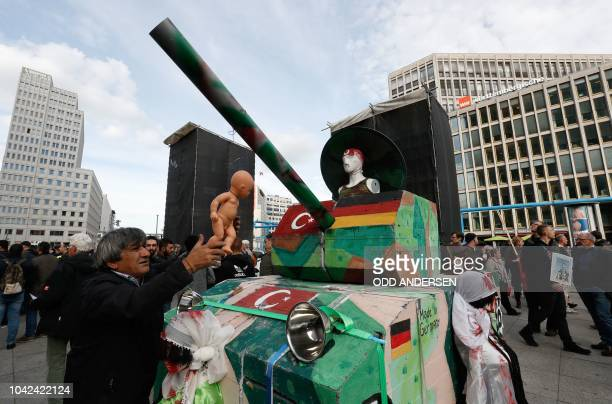 A demonstrator stands next to a mockup tank decorated with a baby doll and the flags of Turkey and Germany in protest against German arms shipments...