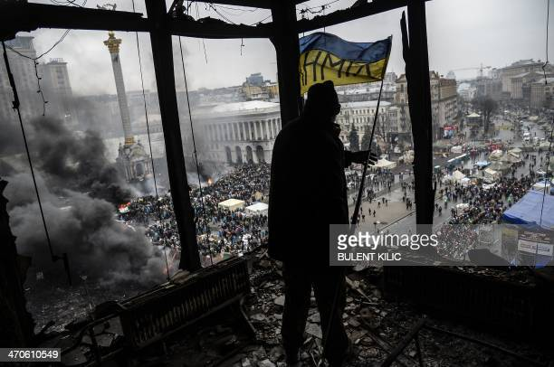 A demonstrator stands on a balcony overlooking Independence square is seen during the face off against heavilyarmed police on February 20 2014 in...
