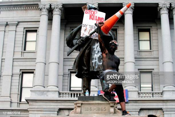 Demonstrator stands on a Civil War statue in Denver, Colorado on May 31 while protesting the death of George Floyd, an unarmed black man who died...