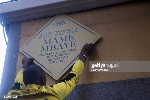 Demonstrator sticks the plaque in memory of Mame Mbaye Protest against institutional racism took place at Nelson Mandela square one year after the...