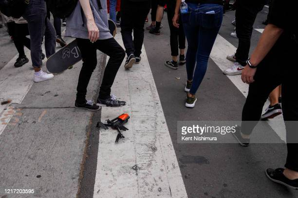 A demonstrator stomps on a drone that lost control after hitting a building and crash landed over protesters at the intersection of 4th street and...