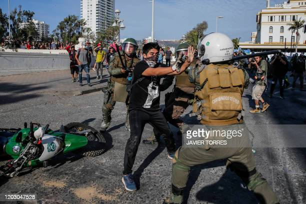 Demonstrator struggles with a riot police on February 24, 2020 during clashes which erupted in a protest against Chile's President Sebastian Pinera...