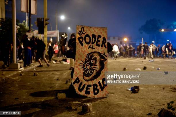 Demonstrator, supporter of Peruvian ousted President Martin Vizcarra, with a shield reading The power to the people takes part in a protest against...