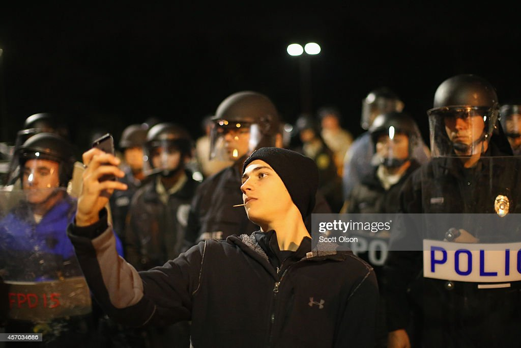 A demonstrator takes a selfie in front of a police line during a protest outside the Ferguson police department on October 10, 2014 in Ferguson, Missouri. Ferguson has been plagued with protests since the death of 18-year-old Michael Brown who was shot and killed by Darren Wilson, a Ferguson police officer on August 9.