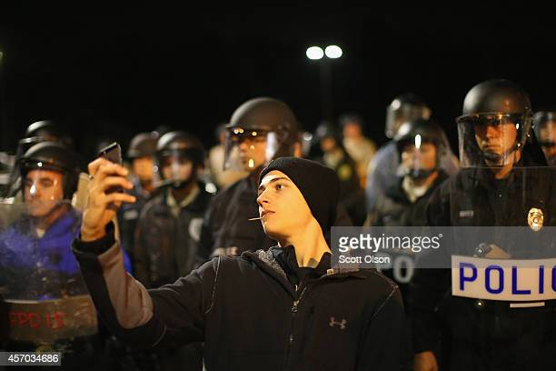A demonstrator takes a selfie in front of a police line during a protest outside the Ferguson police department on October 10 2014 in Ferguson...