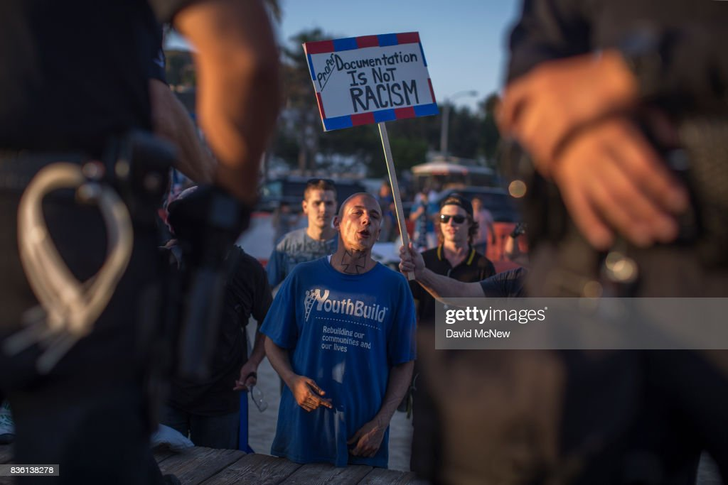 A demonstrator taunts counter demonstrators from behind a line of police separating the two during an 'America First' demonstration on August 20, 2017 in Laguna Beach, California. Organizers of the rally describe it as a vigil for victims of illegal immigrants and refugees. Opponents say the demonstration is steeped in racism.