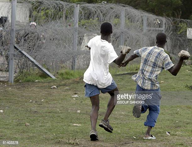 Demonstrator throw stones to French gendarmes 05 October 2004 during a protest at the French military barracks in Abidjan Dozens of hardline...
