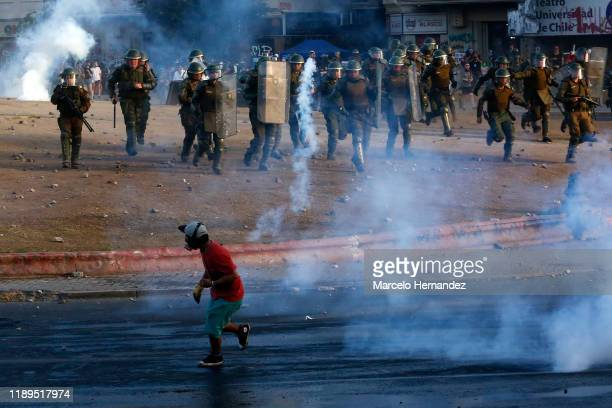 Demonstrator throws a gas bomb to riot police officers during a protest against the government of President Sebastian Piñera on December 18, 2019 in...
