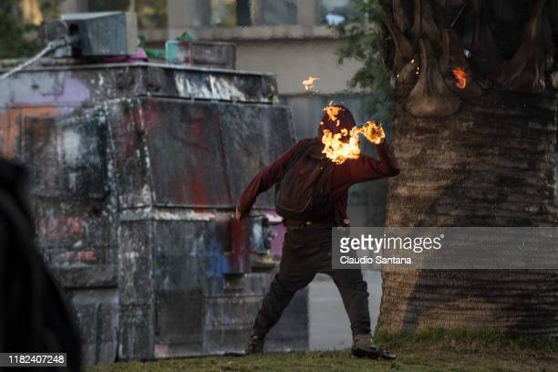 A demonstrator throws a molotov cocktail against riot police water cannon truck during a protest against president Sebastian Piñera to commemorate...