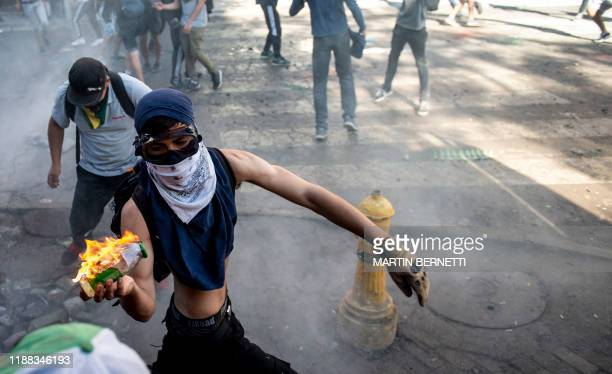 A demonstrator throws a Molotov cocktail at riot police during clashes which erupted during a protest against President Sebastian Pinera's government...