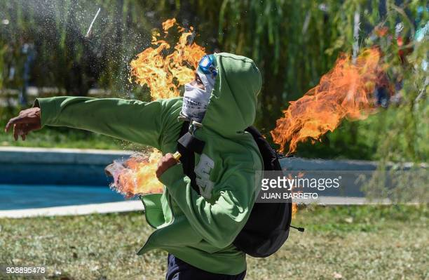 TOPSHOT A demonstrator throws a Molotov cocktail at riot police during clashes in Caracas on January 22 2018 which erupted during a protest to...