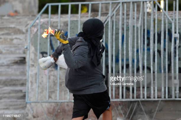 A demonstrator throws a molotov cocktail during a protest against President Sebastian Piñera's policies and the police forces violence on February 7...