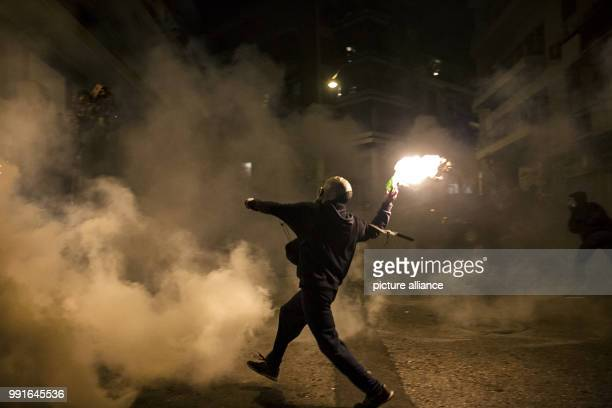 A demonstrator throws a Molotov cocktail towards Greek Riot Police during clashes following a protest against state repression on the 44th...