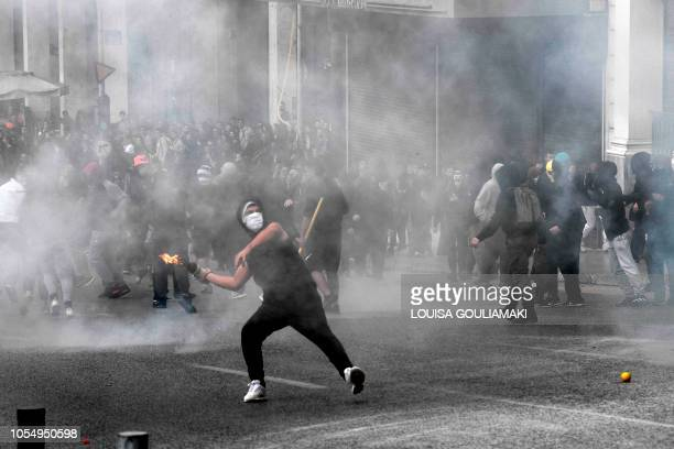 A demonstrator throws a molotov cocktail towards police as high school students rally and protest against the high school educational reform in...