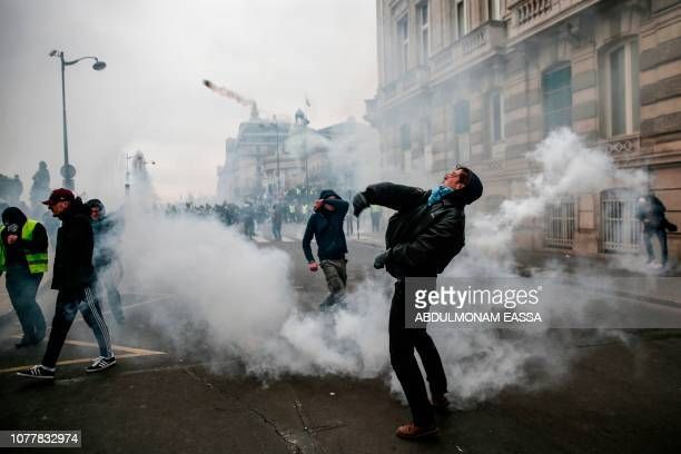 A demonstrator throws a projectile on January 5 2019 in Paris during an antigovernment demonstration called by the yellow vest 'Gilets Jaunes'...