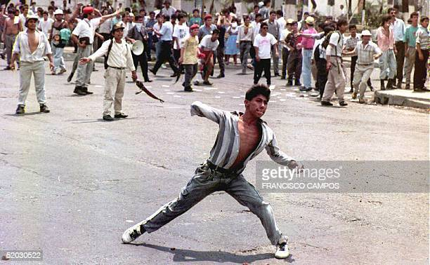 A demonstrator throws a rock 20 May 1993 at antiriot police near the presidential residence Police used tear gas to disperse the protest called by...