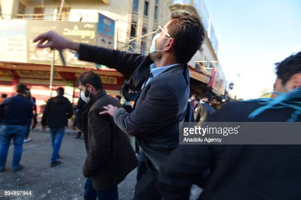 A demonstrator throws a rock at riot police within antigovernment protests in Sulaymaniyah Iraq on December 18 2017 Protests continue as...