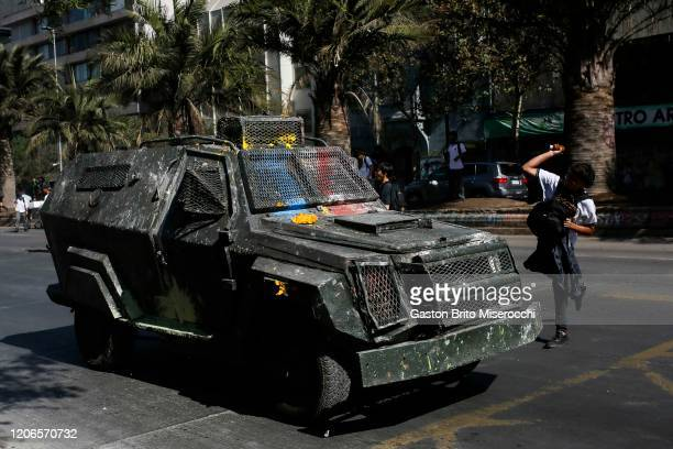 A demonstrator throws a rock to a riot police car during protests against the government of Sebastián Piñera on its second anniversary on March 11...