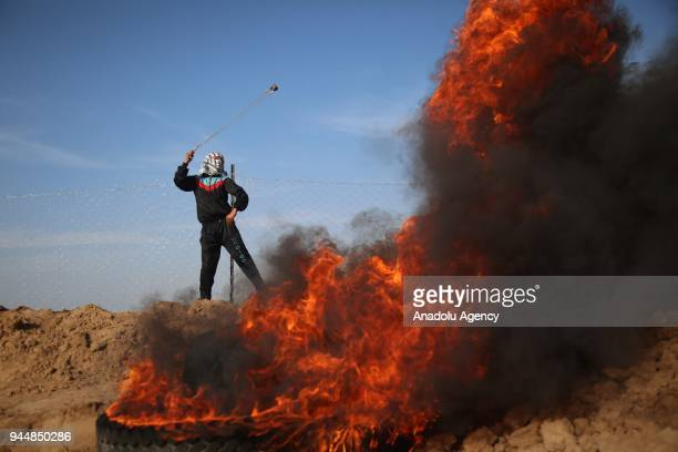 A demonstrator throws a rock with a slingshot and burns tires in response to Israeli soldiers' intervention to remark the 'Great March of Return' at...