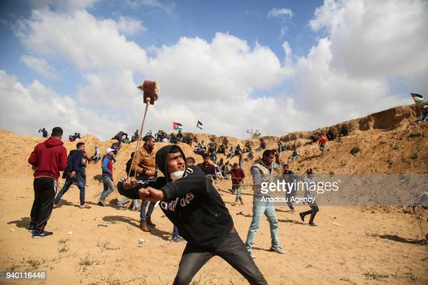 A demonstrator throws a rock with a slingshot in response to Israeli soldiers' intervention in the 'Great March of Return' at the border east of Al...