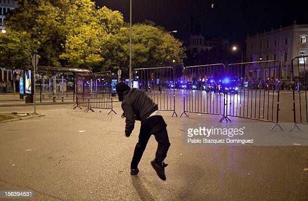 A demonstrator throws a stone at riot police after a protest near the Spanish parliament turned violent on November 14 2012 in Madrid Spain A...