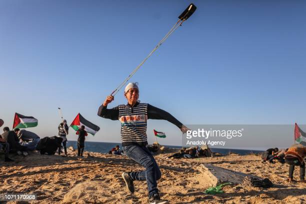 Demonstrator throws a stone in response to Israeli intervention during a protest against Israeli blockade over Gaza on December 10, 2018 at the coast...
