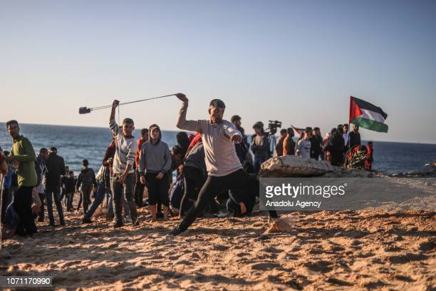 A demonstrator throws a stone in response to Israeli intervention during a protest against Israeli blockade over Gaza on December 10 2018 at the...