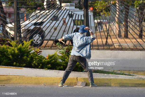 A demonstrator throws a stone to a vehicle of Guardia Nacional on April 30 2019 in Caracas Venezuela Through a live broadcast thru social media...