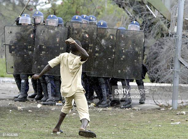 A demonstrator throws a stone to French gendarmes 05 October 2004 during a protest at the French military barracks in Abidjan Dozens of hardline...