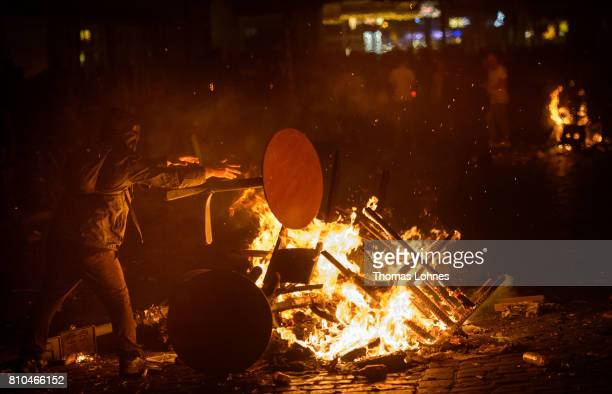 A demonstrator throws a table into a burning crush barrier during a demonstration against the G20 Summit on July 7 2017 in Hamburg Germany Leaders of...