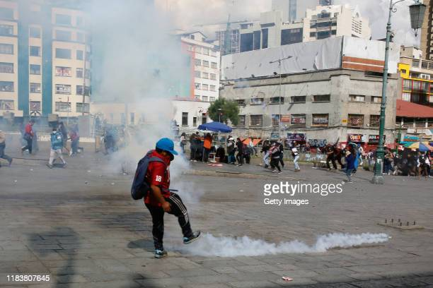A demonstrator throws a tear gas bomb to the police during a funeral procession of the victims killed during clashes with police at the Senkata fuel...