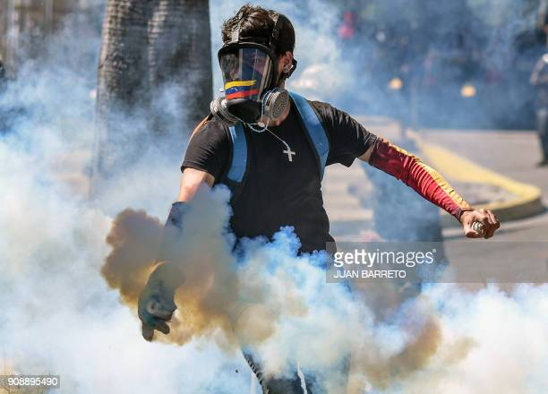 TOPSHOT A demonstrator throws a tear gas canister back at the riot police during clashes in Caracas on January 22 2018 which erupted during a protest...
