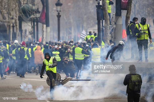 A demonstrator throws a tear gas canister during the demonstration of the yellow vests near the Arc de Triomphe on December 8 2018 in Paris France...