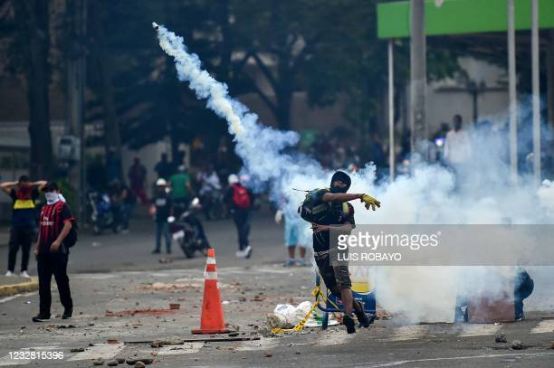 Demonstrator throws a tear gas canister to riot police officers during a protest against the government in Cali, Colombia, on May 10, 2021. - Faced...