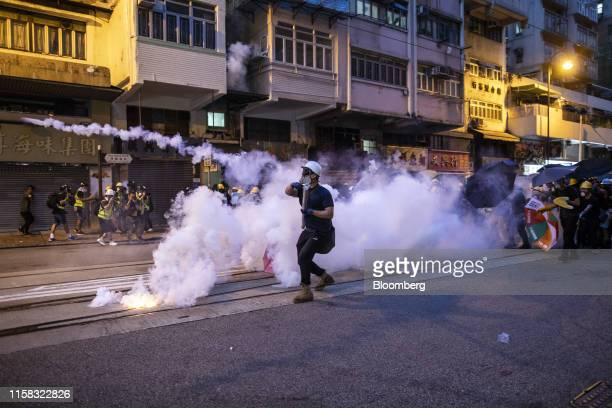 A demonstrator throws a tear gas canister towards riot police on Des Voeux Road West during a protest in the Sai Ying Pun district of Hong Kong China...