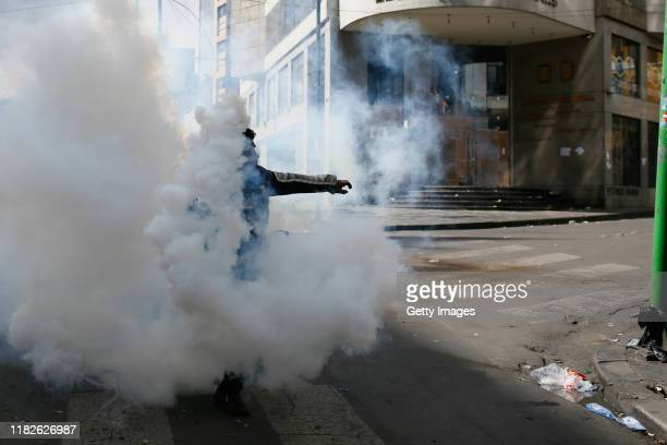 A demonstrator throws back a tear gas bomb to military police on November 15 2019 in La Paz Bolivia Morales flew to Mexico alleging a coup under...