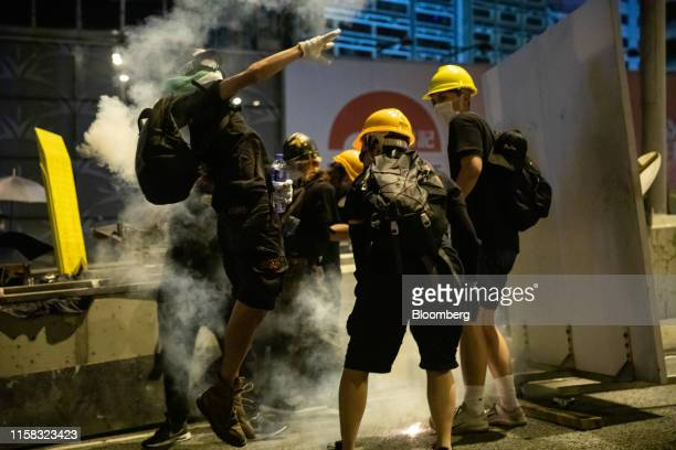 Demonstrator throws back a tear gas canister towards riot police during a protest in Sheung Wan district of Hong Kong, China, on Sunday, July 28,...