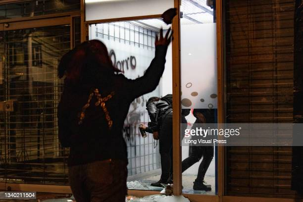 Demonstrator throws rocks and debris as others vandalize an ATM at the Villa Luz CAI police station were police officers tortured Javier Ordonez on...