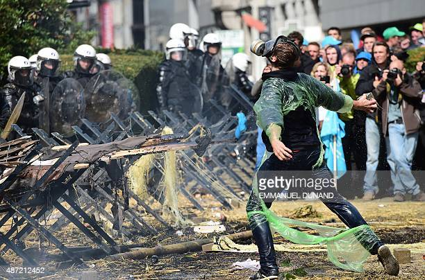 A demonstrator throws rocks on antiriot policemen during a demonstration of farmers in front of the European Commission building on September 7 in...
