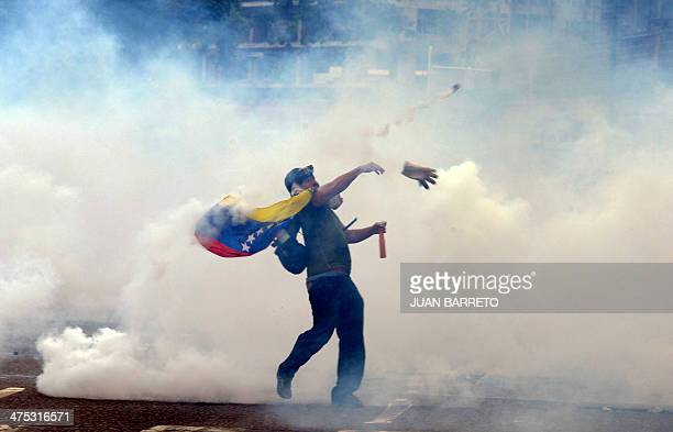 A demonstrator throws stones at riot policemen during an antigovernment protest in eastern Caracas on February 27 2014 Dueling demos of pro and...