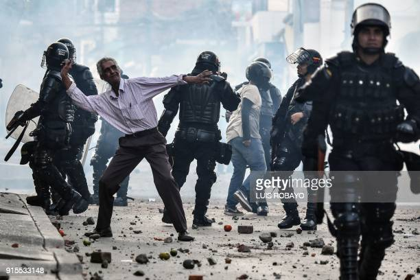 TOPSHOT A demonstrator throws stones during a protest against a campaign rally held for Rodrigo Londono Echeverri known as 'Timochenko' the...