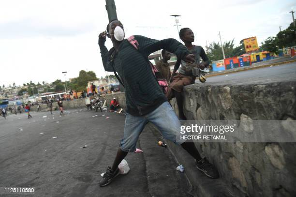 A demonstrator throws stones during clashes with Haitian police in PortauPrince February 15 on the ninth day of protests against Haitian President...