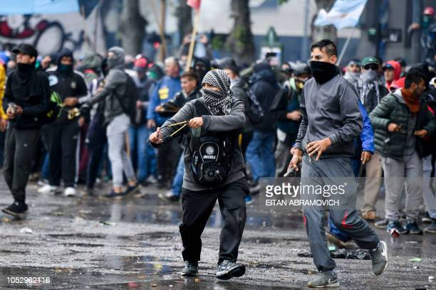 A demonstrator throws stones with a slingshot at riot police outside the Congress while Argentine Deputies began the discussion on the governments...