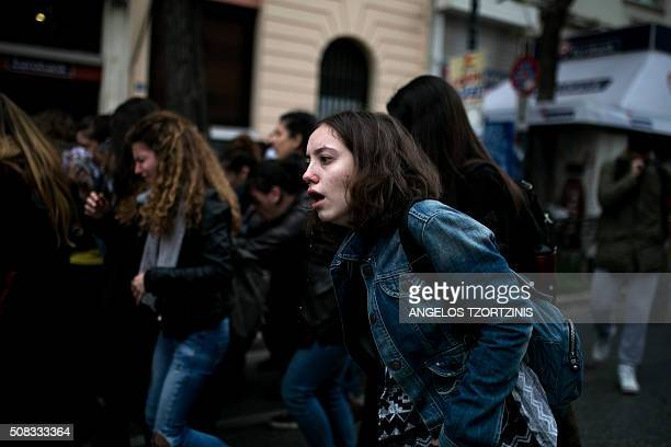 A demonstrator tries to breath after inhaling tear gas during a massive protest in front of the Greek parliament in Athens on February 4 2016...