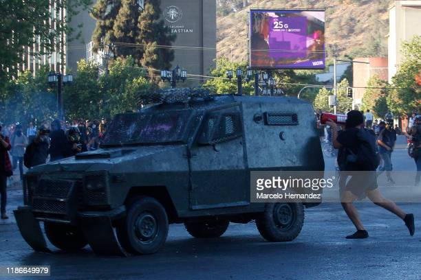Demonstrator tries to hit an armored car with an extinguisher during the protests against president Sebastian Piñera at Plaza Italia on December 5,...