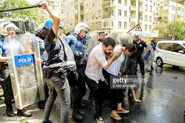 Demonstrator tries to protect Peoples Democracy Party's deputy Feleknas Uca during clashes with Turkish anti riot police during a protest against the...