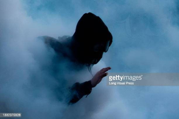 Demonstrator tries to scape a tear gas cloud as demonstrations ended in late-night clashes between riot police and Demonstrators as Colombia marks 3...