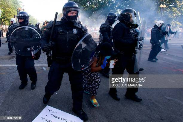 A demonstrator try to pass between a police line wearing riot gear as they push back demonstrators outside of the White House June 1 2020 in...
