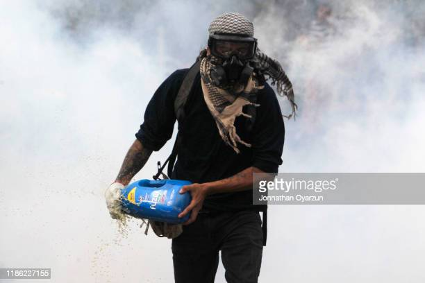 A demonstrator turns off a gas canister during protests against president Piñera at Plaza Italia on December 2 2019 in Santiago Chile To reduce...