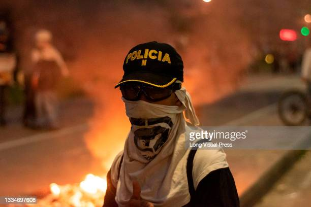 Demonstrator uses a Colombia's police cap during anti-government that ended in clashes between protesters and Colombia's riot police amid the...